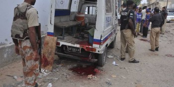 Karachi: 27th May - Security personnel standing near to a damaged police van with blood stains, after three  policemen killed by unidentified gunmen in Karachi on Wednesday. - DNA Photo by Suleman Khan