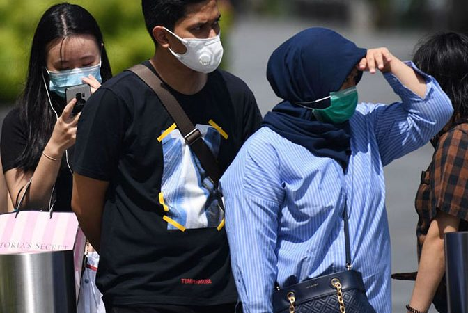 People wearing protective facemasks wait at a pedestrian crossing in Singapore on February 4, 2020. - Singapore has 18 cases of individuals infected with the novel coronavirus, which originated from Wuhan in China late last year. (Photo by Roslan RAHMAN / AFP)
