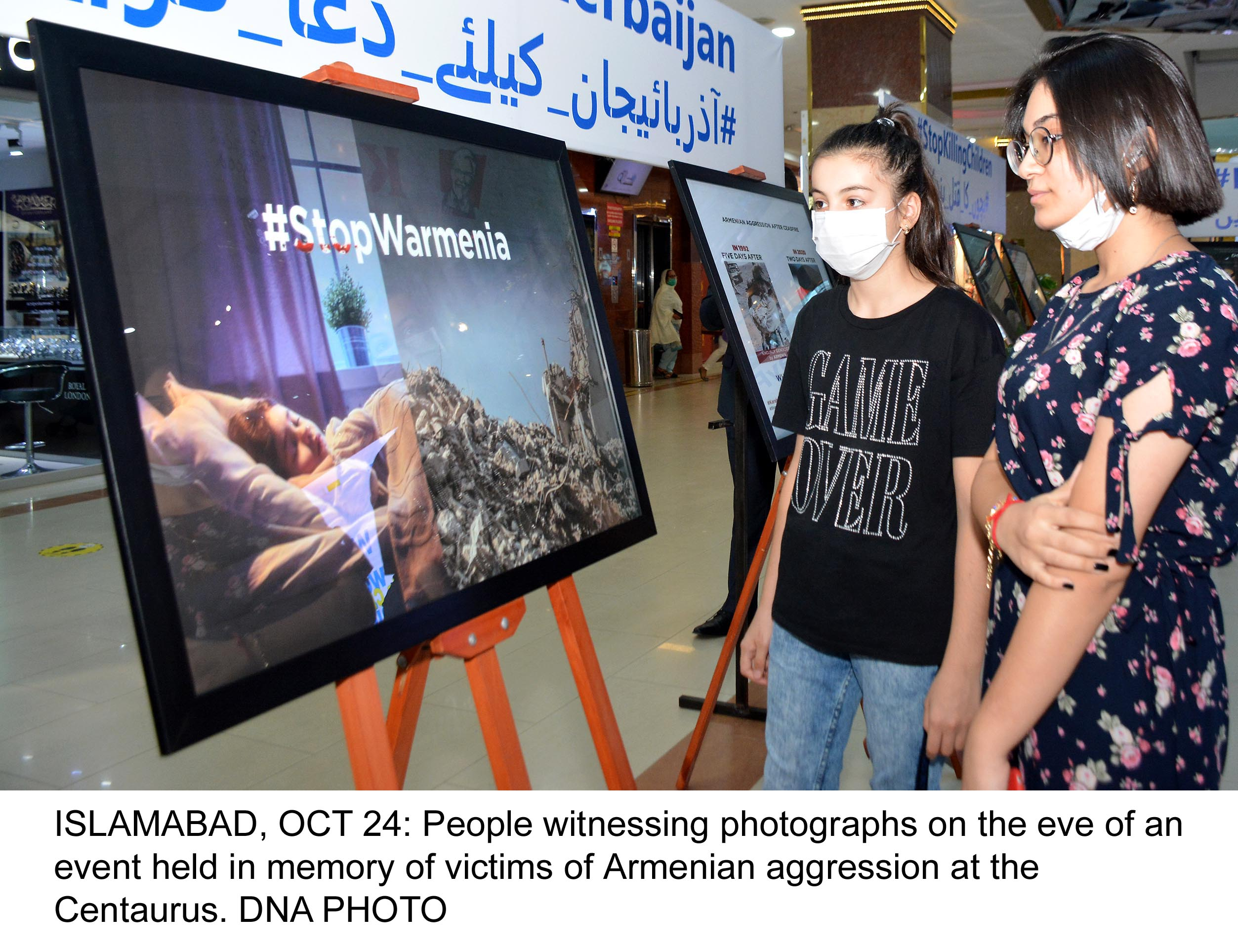 ISLAMABAD, OCT 24: People witnessing photographs on the eve of an event held in memory of victims of Armenian aggression at the Centaurus. DNA PHOTO